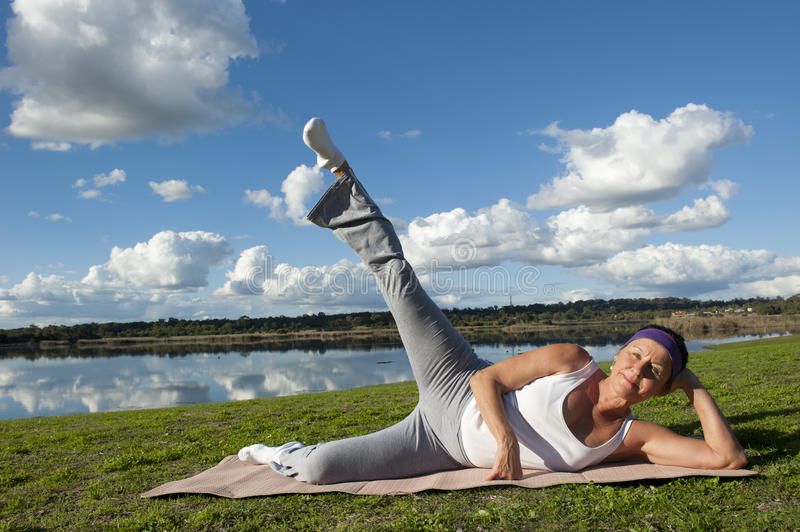 Mature woman practicing yoga looking up, day