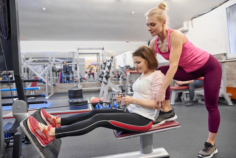 Mature woman doing sport exercises with personal trainer at gym. Female instructor assisting older woman royalty free stock photo