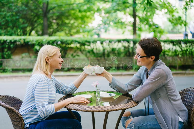 Mature women friends celebrating meeting clinking tea cups in outdoor cafe stock photos