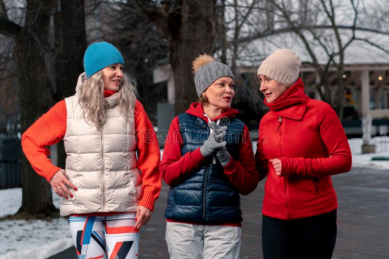 Mature Women Friends Walking In Park After Morning Run And Talking About News. Active Lifestyle at Middle Age. Mature Women Friends Walking In Park After stock image