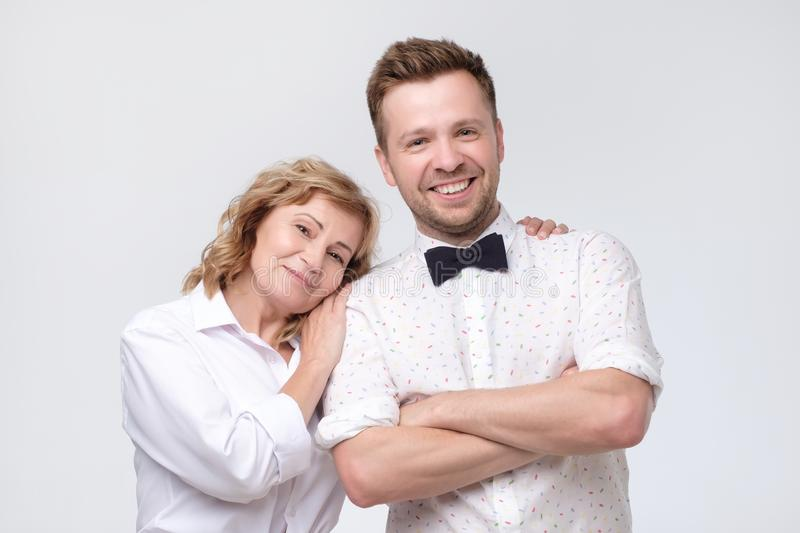 Mature woman hug her young handsome son. stock photos