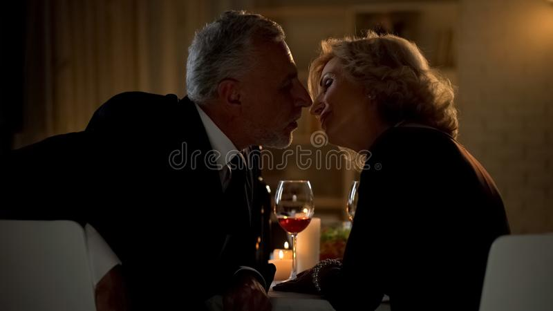 Mature woman and man kissing during date in restaurant, couple closeness, love stock photography