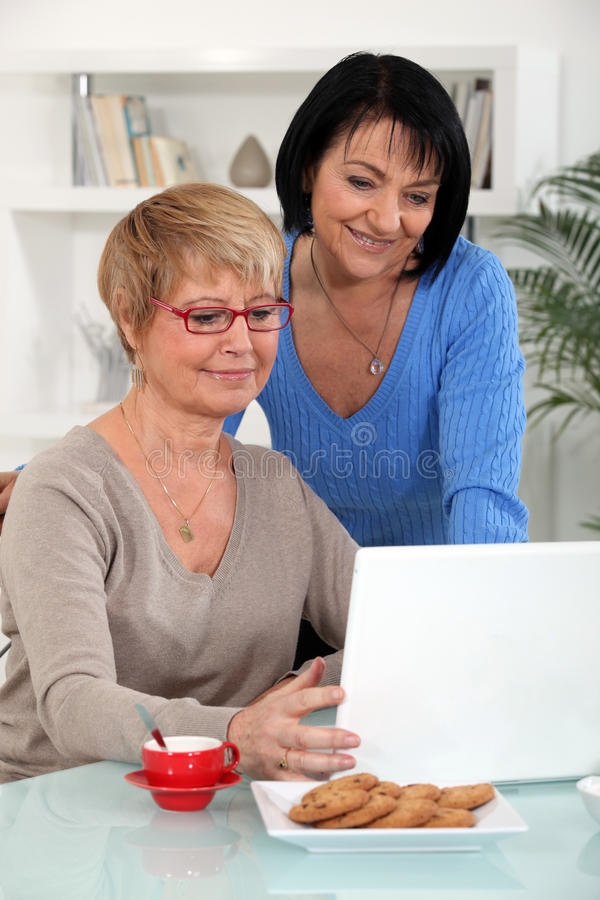 Mature women with a notebook. Mature women in front of a notebook at home stock photography