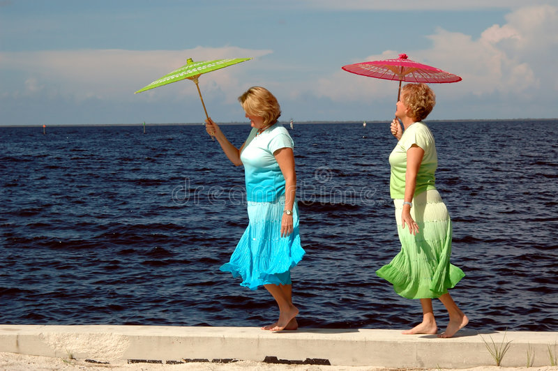 Mature women at seashore. Two mature women walking on a seawall with parasols royalty free stock image