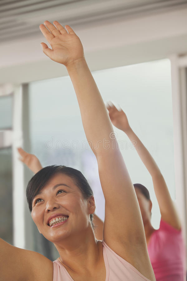 Mature women smiling and exercising in the gym during fitness class royalty free stock images