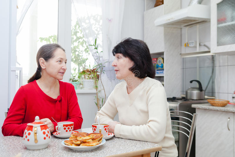 Mature women talking at kitchen. Two mature women talking at kitchen table with cup of tea stock image