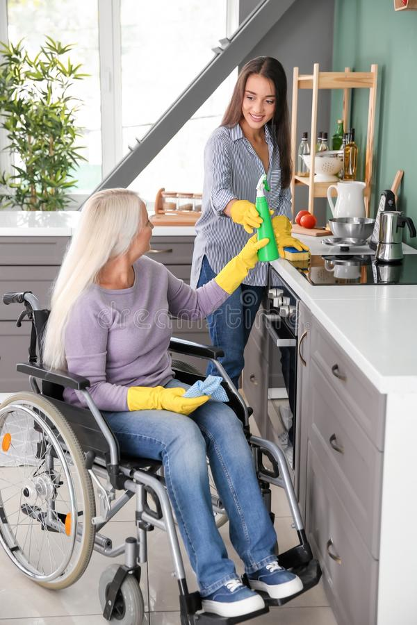 Mature woman in wheelchair cleaning kitchen together with daughter stock photo
