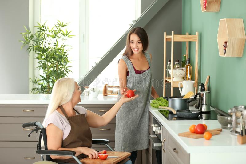 Mature woman in wheelchair cooking together with daughter at home stock images