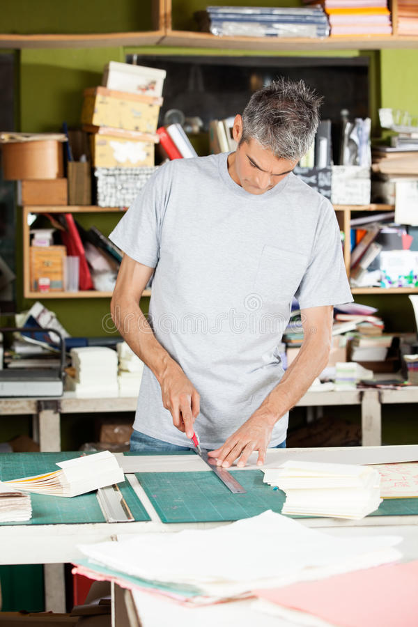 Mature Worker Cutting Paper In Factory royalty free stock photography