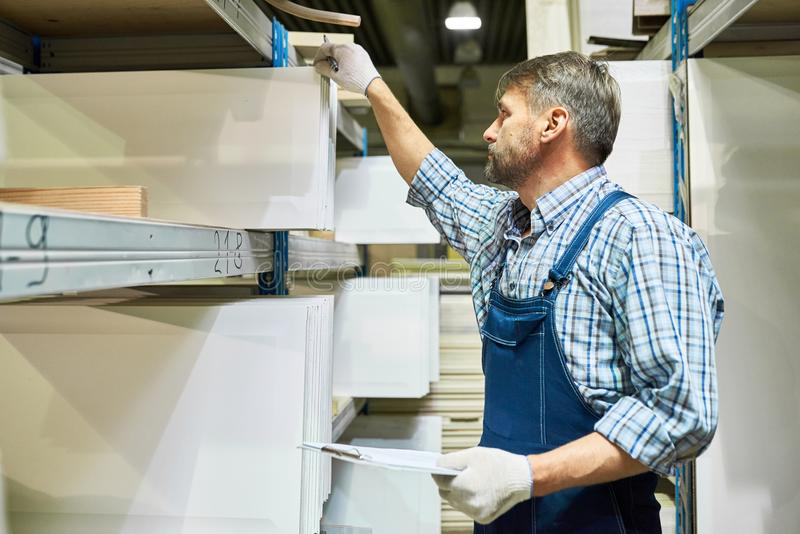 Mature Worker Doing Inventory in Storage Room stock images