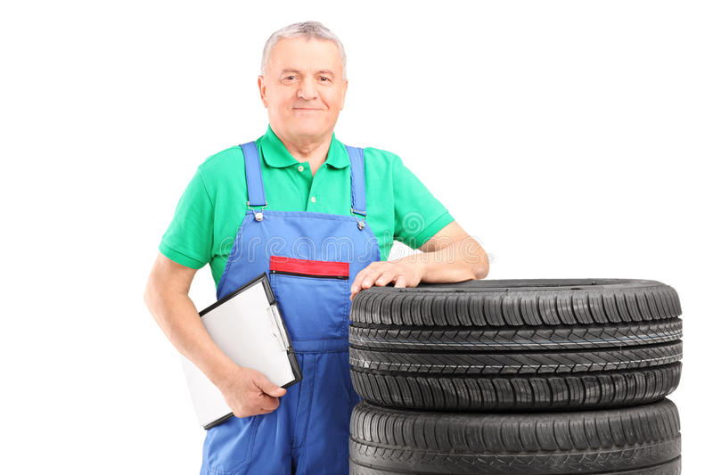 A mature worker posing on car tires with clipboard