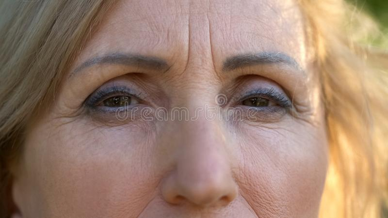Mature wrinkled woman looking at camera, hope and despair in eyes, close up royalty free stock photos