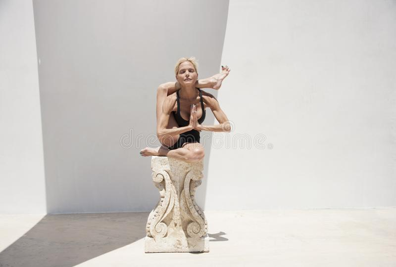 Mature Yoga Woman in Ionic Column Prop Supported Asana royalty free stock photography