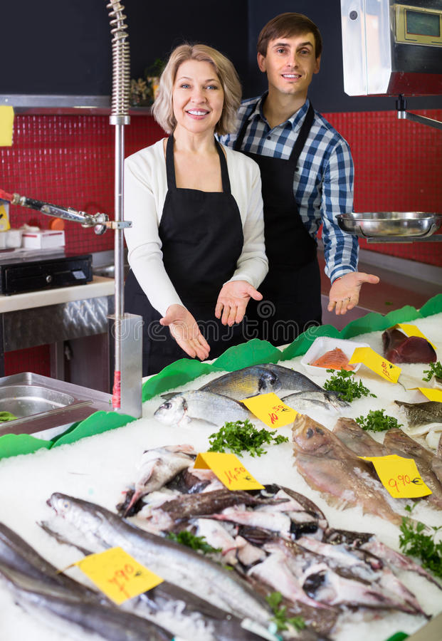 Mature and young sellers posing stock photo