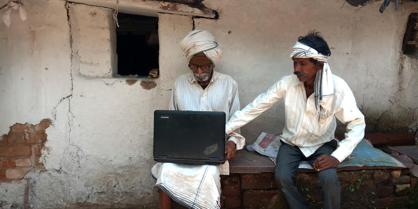 Matured villager learning about laptop computer system. Indian, illiterate, people, operating, seating, courtyard, farmer, capturing, picture, wheat, grain royalty free stock photos