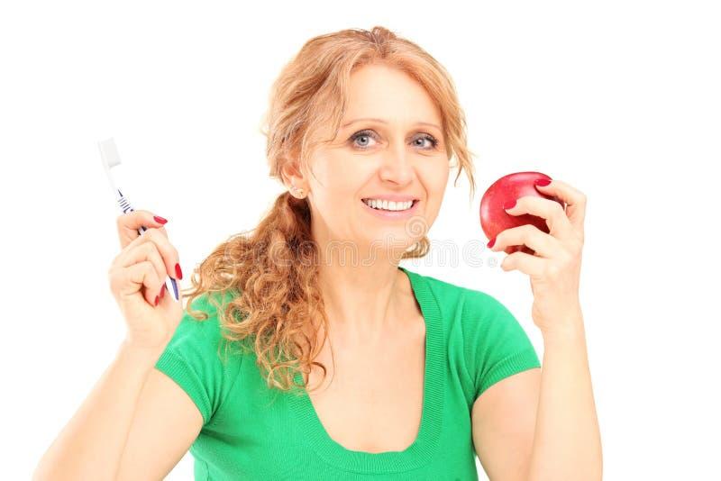 Maturesmiling kobieta trzyma czerwonego toothbrush i jabłka zdjęcia royalty free