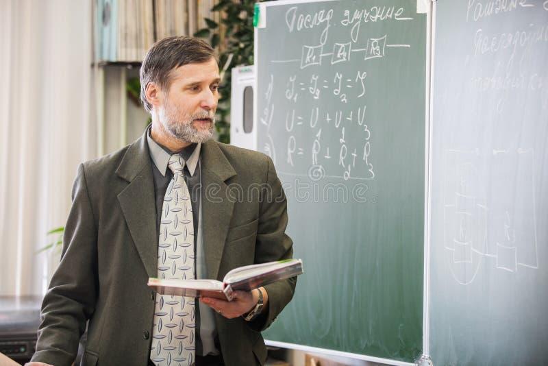 Maturi l'insegnante maschio che spiega il nuovo argomento in physicis fotografia stock libera da diritti