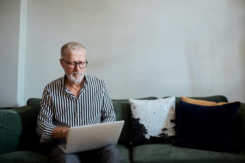 Maturi l'uomo barbuto che lavora dalla casa con il computer portatile sedendosi allo scrittorio vicino alla finestra fotografie stock