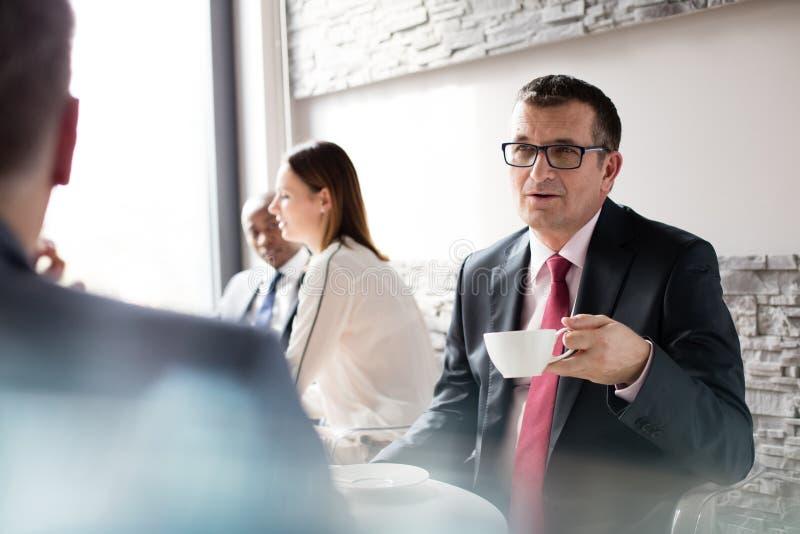 Maturi l'uomo d'affari che mangia il caffè mentre parlano con il collega maschio nel self-service dell'ufficio fotografie stock