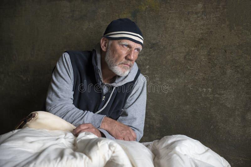 Maturi l'uomo senza tetto che si siede in vecchie coperte all'aperto immagine stock libera da diritti