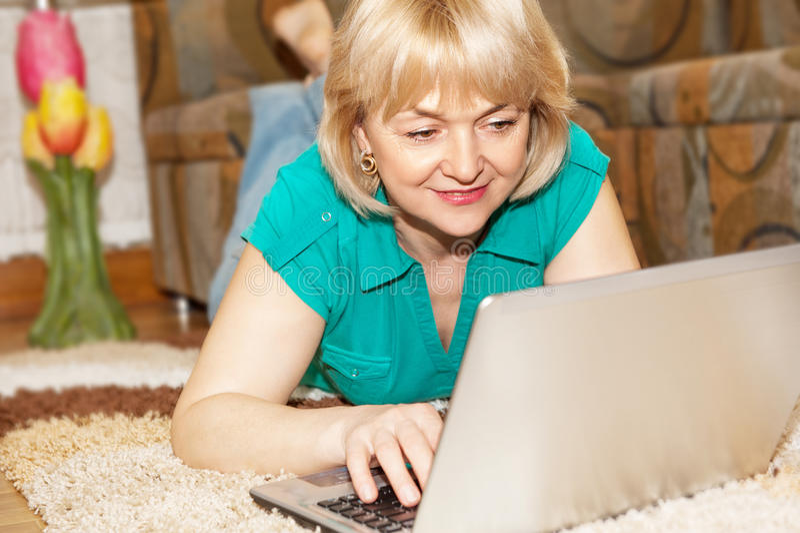 Maturi la donna con il computer portatile fotografie stock libere da diritti