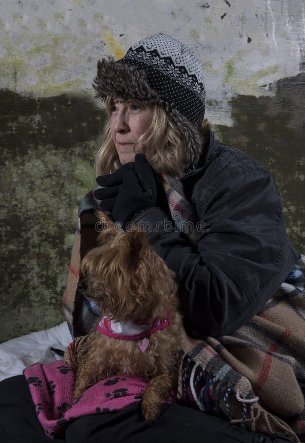 Maturi la donna senza tetto che pende contro una vecchia parete fotografie stock