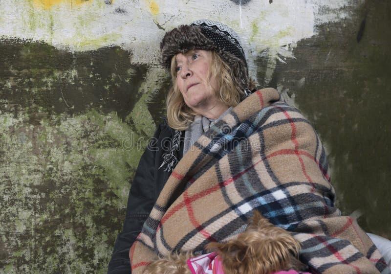 Maturi la donna senza tetto che pende contro una vecchia parete immagini stock