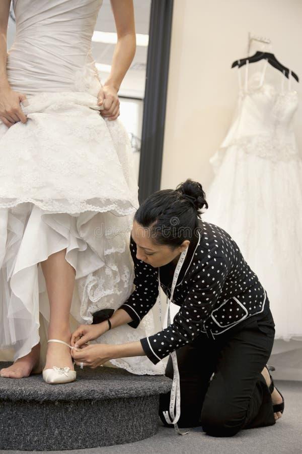 Maturi la sposa d'aiuto degli impiegati femminili con calzature in boutique nuziale fotografia stock libera da diritti
