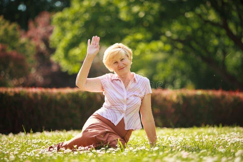 Maturidade. Mulher europeia do cabelo branco que senta-se na grama e que tem o divertimento imagem de stock