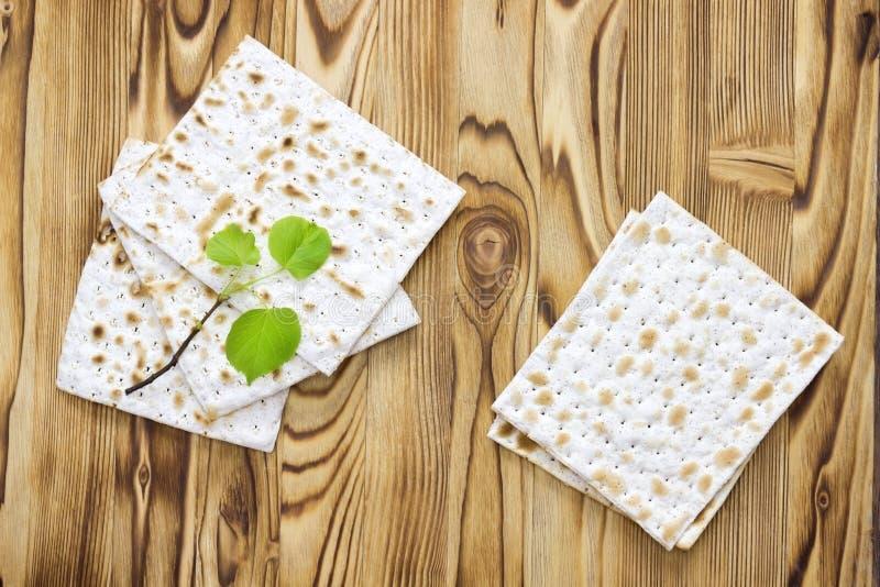 matzah或matza片断一张顶上的照片和一棵小春天新鲜的椴树分支 在木桌上的Matzah犹太的 图库摄影