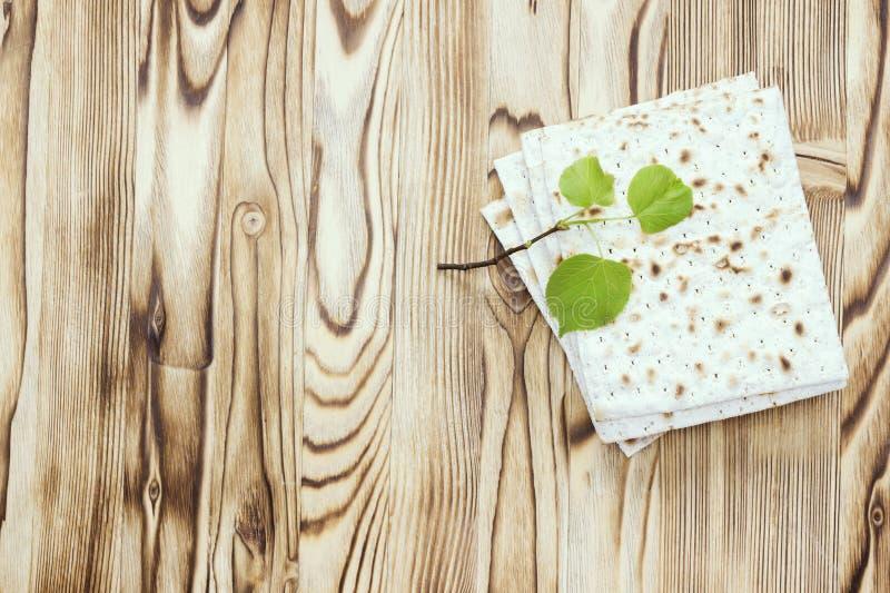 matzah或matza片断一张顶上的照片和一棵小春天新鲜的椴树分支 在木桌上的Matzah犹太的 免版税图库摄影
