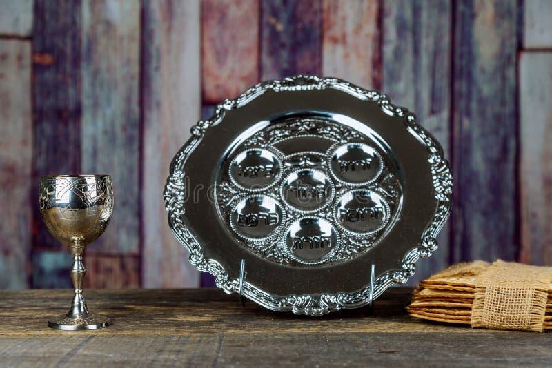 Matzah judío de Pesach de la pascua judía de los días de fiesta y una taza de plata llena de vino con una bendición tradicional foto de archivo libre de regalías