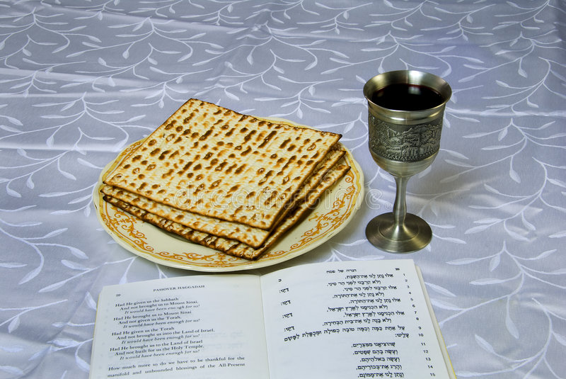 Matzah, wine and haggadah. Passover matzo next to a kiddush cup of wine and traditional text of passover haggadah for the traditional meal known as a seder royalty free stock photo