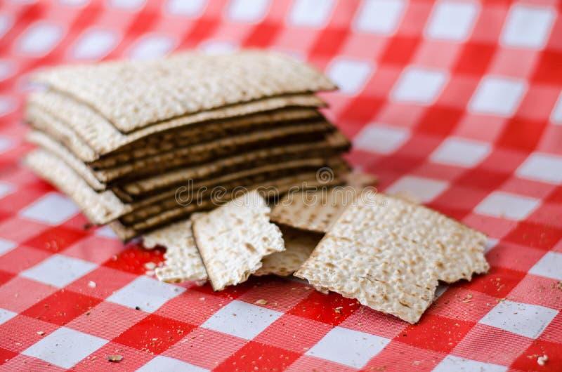 Matzoth y pila agrietados de matzoth detrás, migas alrededor, comida tradicional judía fotos de archivo libres de regalías