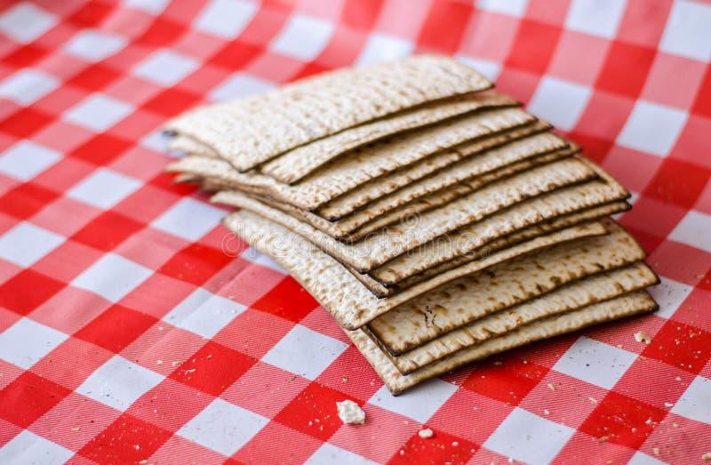 Matzoth y pila agrietados de matzoth detrás, migas alrededor, comida tradicional judía imágenes de archivo libres de regalías