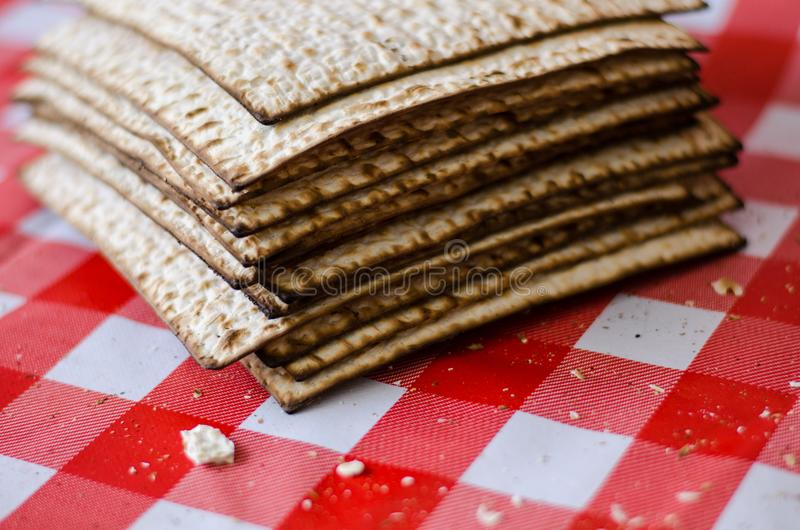 Matzoth y pila agrietados de matzoth detrás, migas alrededor, comida tradicional judía fotografía de archivo