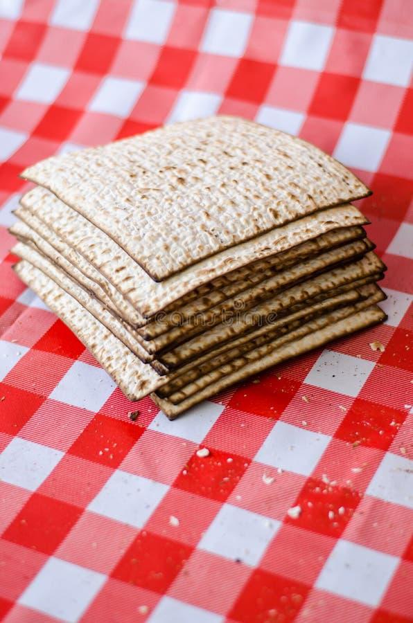 Matzoth y pila agrietados de matzoth detrás, migas alrededor, comida tradicional judía del día de fiesta foto de archivo