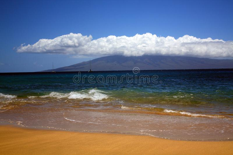 Maui Hawaii with clouds and beach front. Blue clear water and blue clear sky with row of white fluffy clouds over the mountain tops. Two sailboats in the ocean stock images