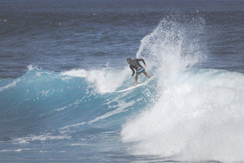 MAUI HI - MARS 10, 2015: Den yrkesmässiga surfaren rider en jätte- wav arkivfoton