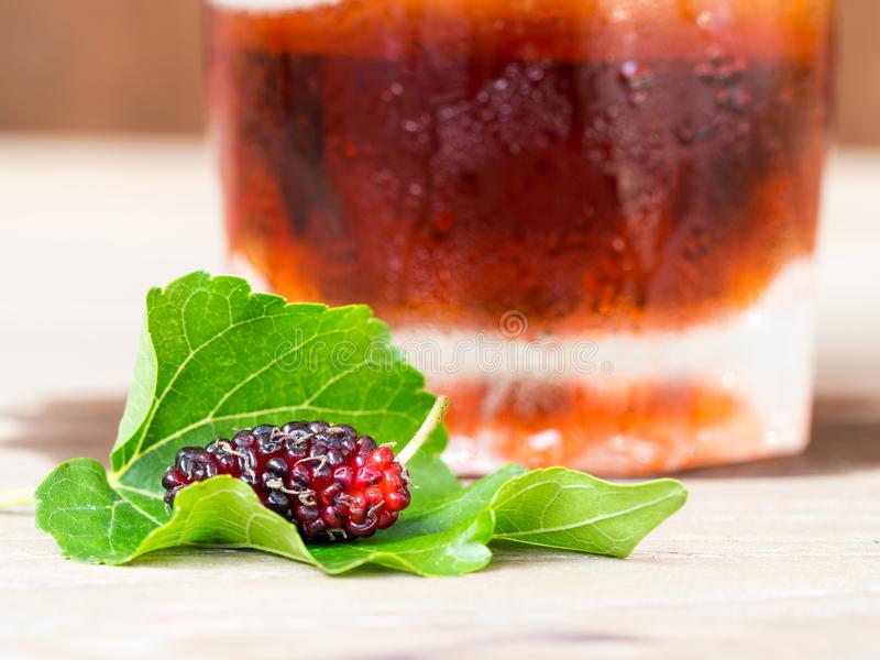 Maulbeeren mit grünem Urlaub auf dem Holztisch vor dem Glas des Maulbeerwassers und -eises Maulbeere dieses eine Frucht lizenzfreies stockfoto