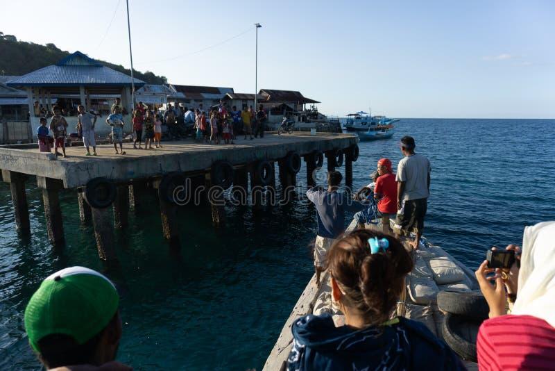 MAUMERE/INDONESIA- 26 ΑΠΡΙΛΊΟΥ 2014: Μια βάρκα προετοιμάζεται να ελλιμενίσει στην αποβάθρα όπου πολλά παιδιά περιμένουν την άφιξή στοκ εικόνα με δικαίωμα ελεύθερης χρήσης