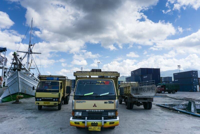 28 maumere/indonesia-APRIL 2014: Drie vrachtwagens die goederen dragen werden geparkeerd in de haven van Maumere op een duidelijk royalty-vrije stock foto