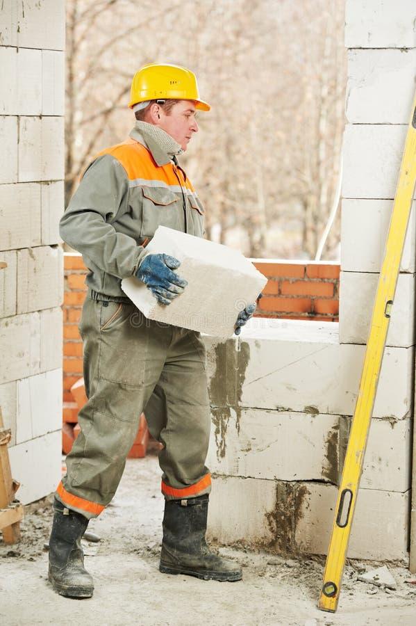 Maurer bei den Aufbaumaurerarbeitarbeiten lizenzfreies stockbild