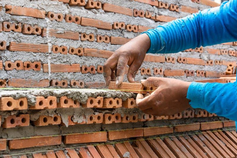 Maurer, der Ziegelstein für Bau vergipst und setzt stockfotografie