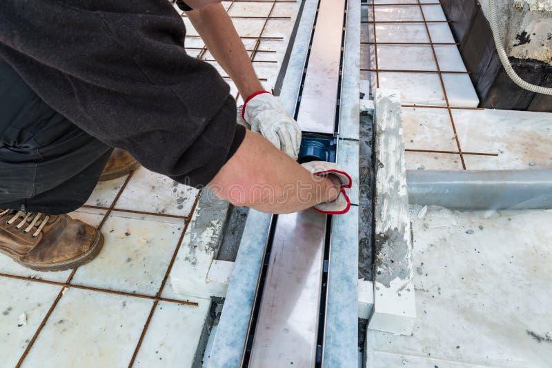 Maurer installiert einen Abflusssinkkasten auf eine Terrasse lizenzfreies stockbild
