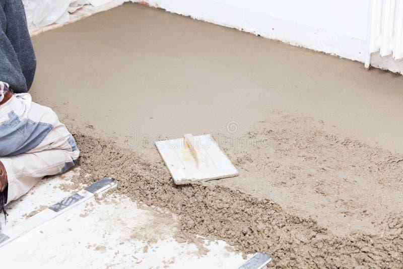 Maurer machen den Zementestrich glatt stockfotografie