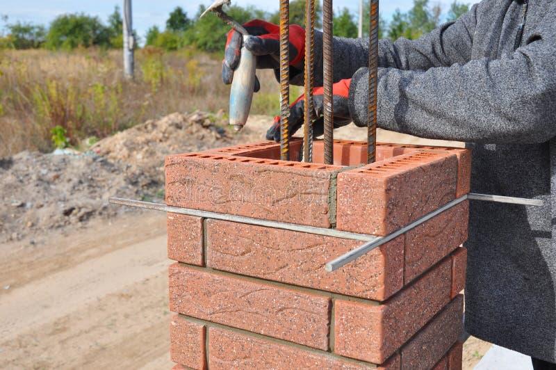 Maurer-Worker Installing Red-Klinker-Blöcke um Eisenstange stockbild