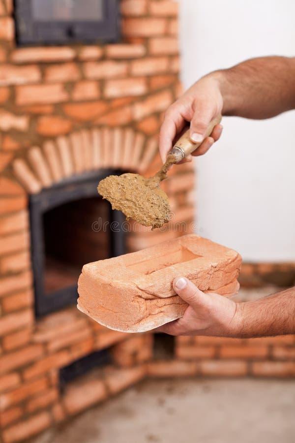 Maurerarbeitarbeitskrafthände mit Ziegelstein- und Lehmmörser auf Kelle lizenzfreie stockfotos