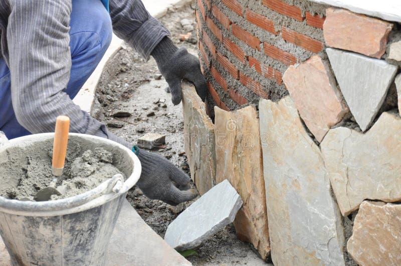 Maurerarbeitskraft, die Steinplatten auf Backsteinmauer mit Mörser installiert stockbilder