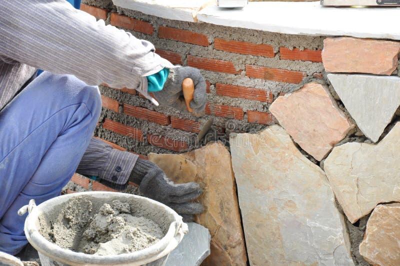 Maurerarbeitskraft, die Steinplatten auf Backsteinmauer w installiert lizenzfreie stockbilder